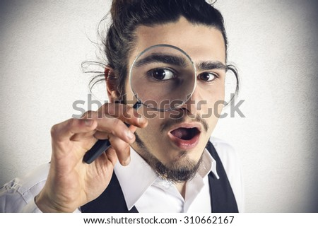 Astonished young man looks through a magnifying lens - stock photo