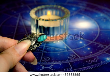 astrology horoscope with candle and woman hand keeping a magic talisman - stock photo