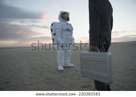 Astronaut and businessman greeting each other - stock photo