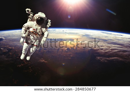 Astronaut in outer space above the earth during sunset. Elements of this image furnished by NASA. - stock photo