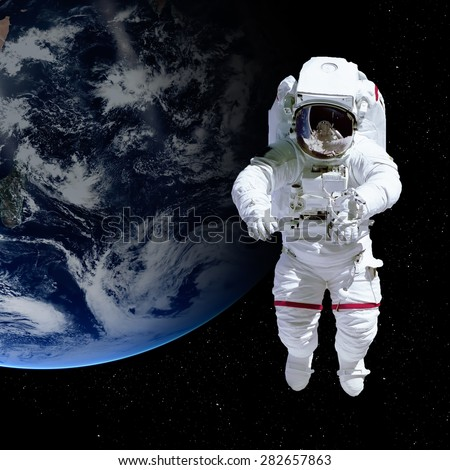 Astronaut in outer space against the backdrop of the planet earth. Elements of this image furnished by NASA. - stock photo