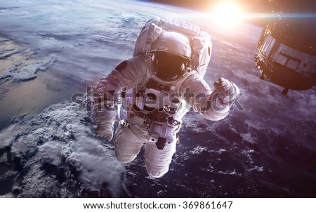 Astronaut in outer space against the backdrop of the planet earth. Elements of this image furnished by NASA - stock photo