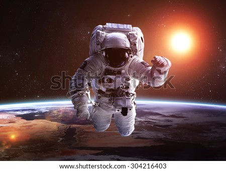 Astronaut in outer space against the backdrop of the planet. Elements of this image furnished by NASA. - stock photo