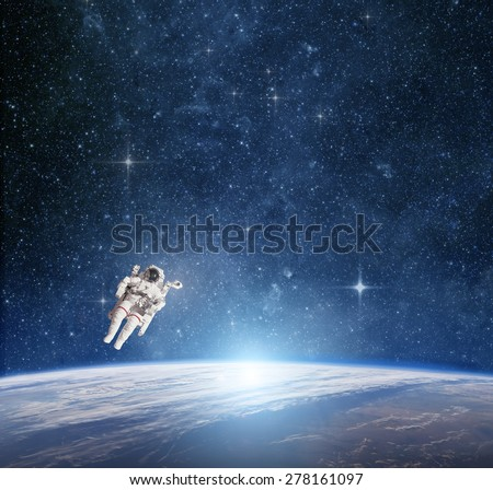 Astronaut in outer space against the  planet earth. Elements of this image furnished by NASA. - stock photo