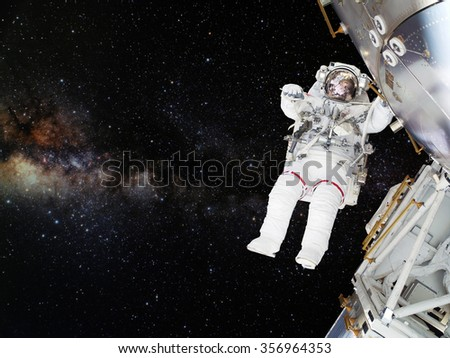 Astronaut on space mission with the outer space on the background. Elements of this image furnished by NASA. - stock photo