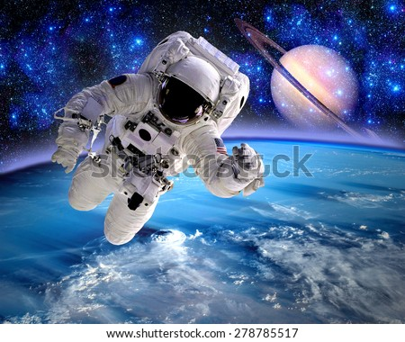 Astronaut spaceman cosmonaut suit space Saturn planet. Elements of this image furnished by NASA. - stock photo