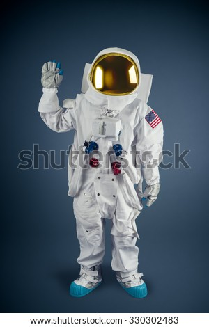 Astronaut waving on a grey background - stock photo