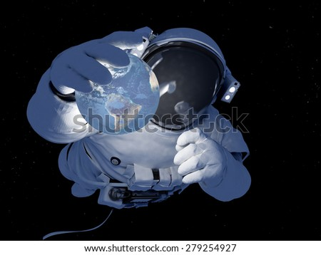 Astronaut with a planet in her hand. - stock photo