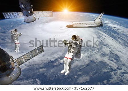 Astronauts, space shuttle and station in outer space - Elements of this image furnished by NASA - stock photo
