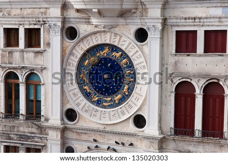 Astronomical clock with statues and roman numbers on a building in Venice. Venezia a city in  Italy small islands separated by canals and linked by bridges. city and lagoon is World Heritage Site. - stock photo
