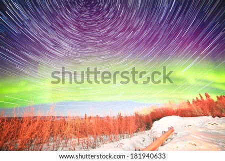 Astrophotography star trails with green glowing display of Northern Lights or Aurora borealis in Fairbanks Alaska - stock photo