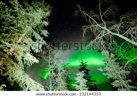 Astrophotography star trails with green glowing display of Northern Lights or Aurora borealis over boreal forest or taiga of Yukon Territory  Canada - stock photo