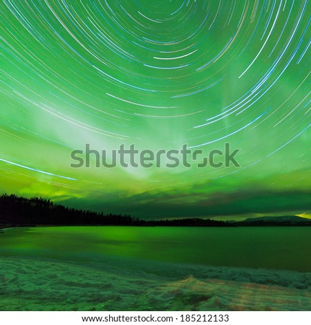 Astrophotography star trails with green sparkling show of Aurora borealis or Northern Lights over boreal forest taiga winter scene of Lake Laberge, Yukon Territory, Canada - stock photo