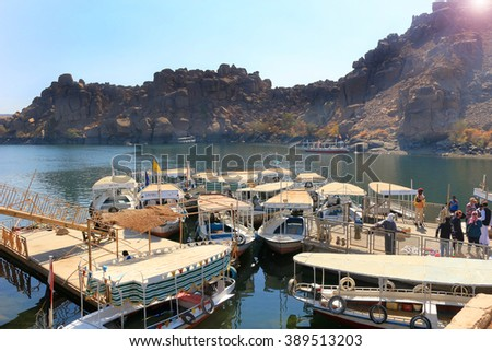 ASWAN, EGYPT - FEBRUARY 1, 2016: Wooden boats carrying passengers docked along the Nile River at the Temple of Philae  in Egypt, North Africa - stock photo