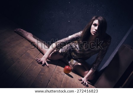 Asylum. Lonely mad woman with red apple sitting on a floor. Low key. - stock photo