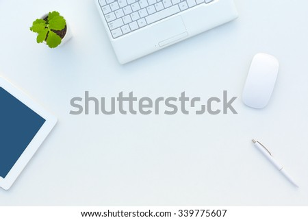 Asymmetrical Business Composition on White Office Desk with Flower Computer Laptop Cropped Tablet PC Mouse and Pen - stock photo