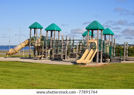 At a park playground with a giant jungle gym. - stock photo