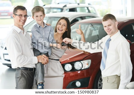 At automobile sales centre. Car salesperson selling new automobile to young family with child boy - stock photo