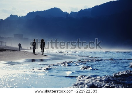At cold evening people walking on the beach touching ocean waves, silhouette of the people walking on the sand, amazing dark silhouette of mountains around bay, wet sand and sea breeze in cold color - stock photo