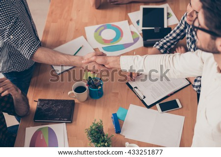 at conference  young  businesspeople shake hands to each other, top-view photo - stock photo