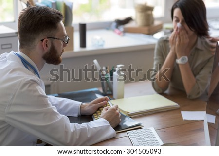 At doctor office. Doctor prescribing medication to patient - stock photo