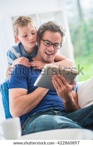 At home, a father and his young son surfing on a tablet, dad sits on a white couch and the boy looks at the screen over the shoulder of his father - stock photo