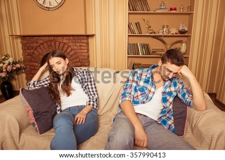at home a young couple sitting on the couch at loggerheads - stock photo