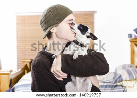 At home portrait of a small dog kissing his male owner. Pet love - stock photo