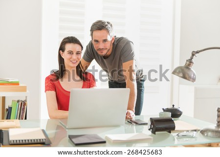 At office, businessteam examining a project together on a laptop, the office is modern and bright - stock photo