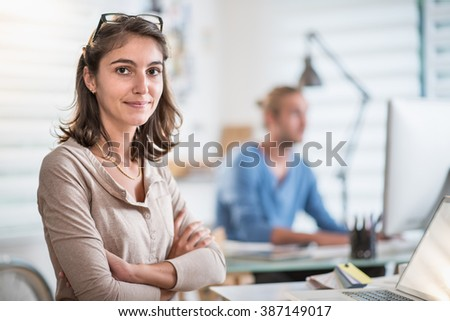 At office, two young people working on their computers, focus on the woman at foreground, she looks at camera. Shot with flare - stock photo