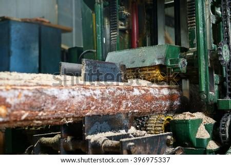 At sawmill. Image of sawing log on machine - stock photo