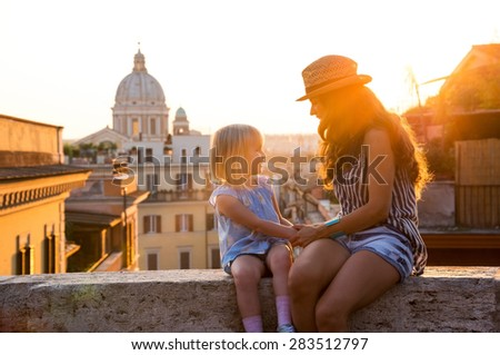 At sunset, a brunette mother wearing summer clothing and a hat and a blonde daughter are sitting holding hands and talking while sitting on a ledge. In the distance, St. Peter's Basilica. - stock photo