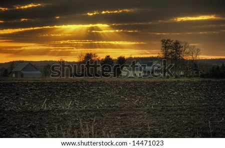 At sunset, sun beams through the clouds over a little farm. - stock photo