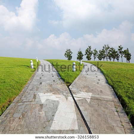 At the crossroad of a stone road leading into a green horizon. - stock photo