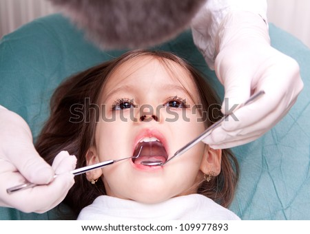at the dentist - little girl have dental examination - stock photo
