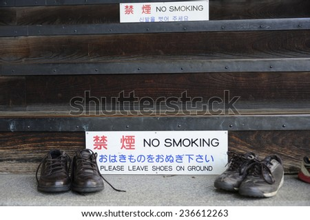 At the entrance of a temple in Japan you are requested to leave your shoes outside and do not smoke - stock photo