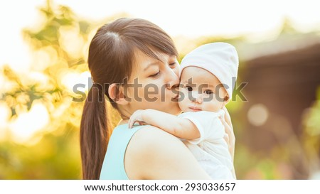 At the evening time before the sunset, 4 months baby feeling happy and smiles with her mother in the garden. - stock photo