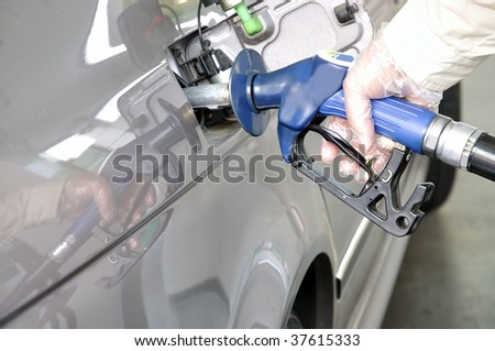 At the petrol station. Closeup of a man's hand using a petrol pump to fill his car up with fuel. - stock photo