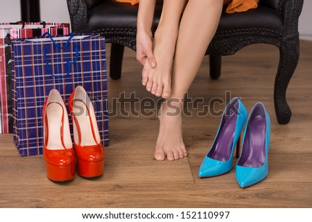 At the shoe store. Close-up of woman sitting at the chair and touching her foot while shoes lying on the floor - stock photo