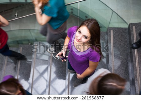 At the university/college - Students rushing up and down a busy stairway - confident pretty young female student looking upwards while listening to music on her mp3 player (color toned image) - stock photo