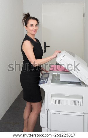 At work, woman with a copy machine - stock photo