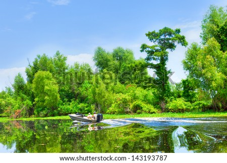 Atchafalaya River Basin, with Cypress trees and boaters. - stock photo