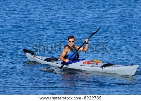 Atheltic man is kayaking in cal blue waters of Mission Bay, San Diego, Califronia. Copy space on top. - stock photo