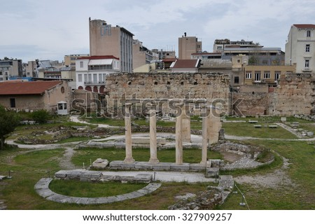 ATHENS, GREECE - APRIL 24, 2015: Columns at the ancient agora and modern city buildings. - stock photo