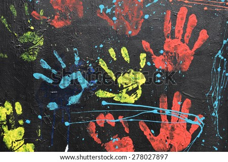 ATHENS, GREECE - APRIL 27, 2015: Messy handprints and dripping paint on textured wall background. Colorful hand imprints abstract graffiti pattern. - stock photo