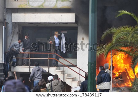 ATHENS - GREECE DEC. 08. A bank office is in fire after an arson attack, during mass riots and the residents of the building are trying to escape, in Athens, December 07, 2008.  - stock photo