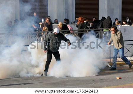 ATHENS, GREECE- DEC. 12 Protesters trying to avoid tear gas canister, during demonstration, in the centre of Athens,, in Athens, December 10, 2008.  - stock photo