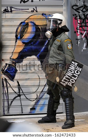 ATHENS, GREECE - DECEMBER 07. Riot police officer wearing a gas mask in front of graffiti of a gas mask, during clashes in Athens, December 07, 2008. - stock photo