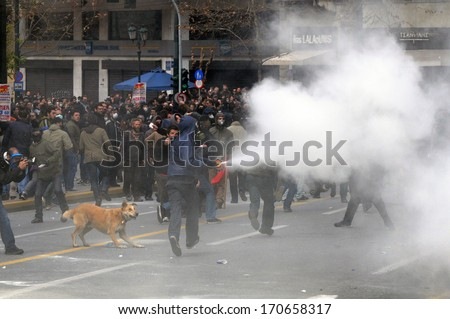 ATHENS, GREECE-FEB.23.  Protester emptying fire extinguisher on riot police during demonstration in Athens, February 23, 2011. - stock photo