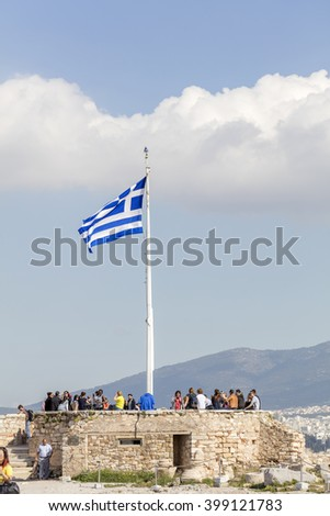 ATHENS, GREECE - FEB 8  2016: Visitors on the famous Acropolis under a blue sky. In the foreground the Greek flag waving. - stock photo
